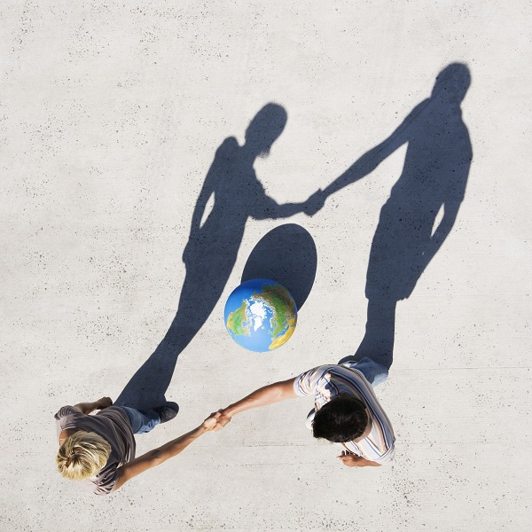 Aerial View of two people shaking hands with shadow and globe outdoors
